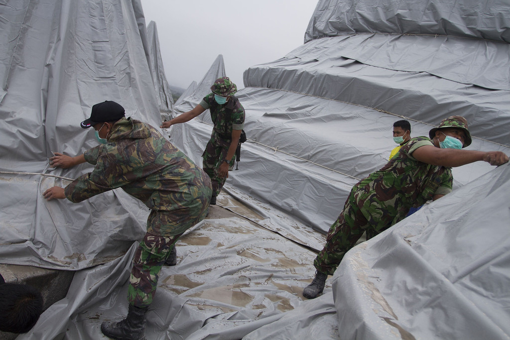 . Indonesian soldiers wrap stupas of the ancient Borubudur temple in Central Java province to protect from the rain of volcanic ash from Mount Kelud volcano on February 14, 2014. AFP PHOTO / SURYO  WIBOWO/AFP/Getty Images
