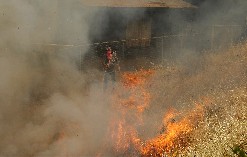 . A ranch worker uses a garden hose to stop the flames from getting to the barn during the second day of the Springs Fire in the mountain areas of Ventura County CA.  May 3, 2013. A fierce, wind-whipped brush fire spread on Friday along the California coast northwest of Los Angeles, threatening several thousand homes and a military base as more than 1,100 dwellings were ordered evacuated and a university campus was closed. May 2,2013. Ventura County California.  Photo by Gene Blevins/LA Daily News