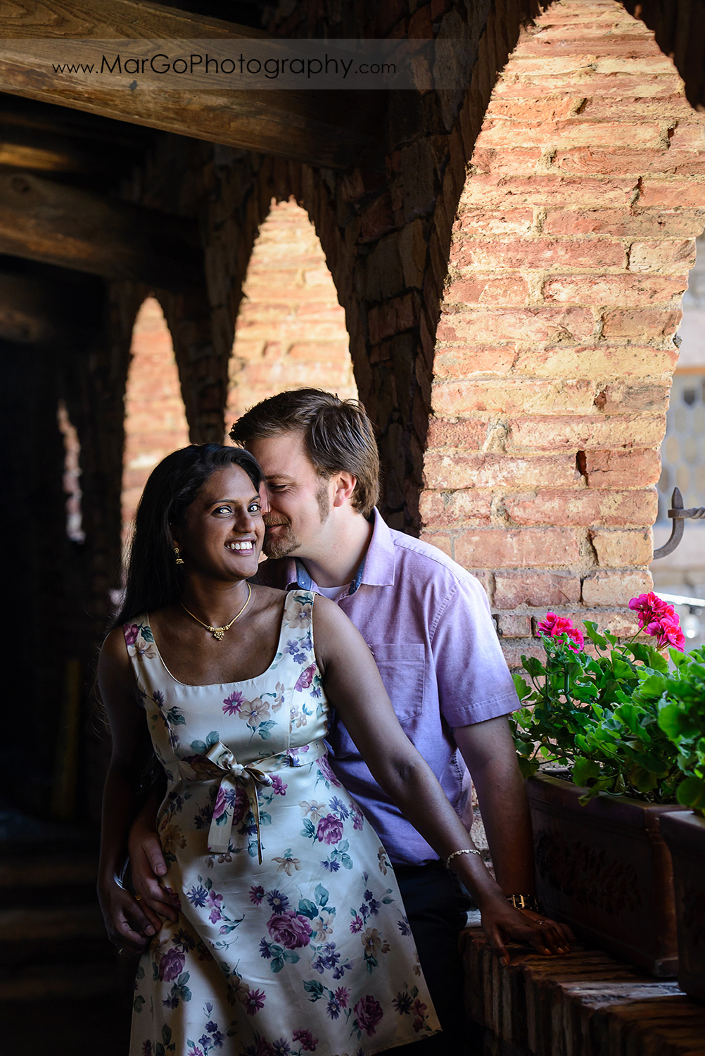portrait of man in pink shirt kissing Indian woman in flower dress looking into camera during engagement session at Castello di Amorosa in Calistoga