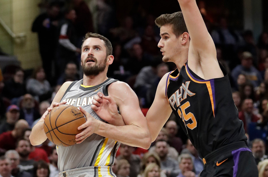 . Cleveland Cavaliers\' Kevin Love, left, drives past Phoenix Suns\' Dragan Bender during the second half of an NBA basketball game Friday, March 23, 2018, in Cleveland. The Cavaliers won 120-95. (AP Photo/Tony Dejak)