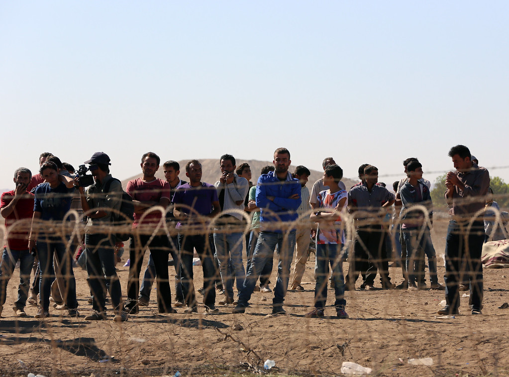 . Syrian refugees wait at the border in Suruc, Turkey, Sunday, Sept. 21, 2014. Turkey opened its border Saturday to allow in up to 60,000 people who massed on the Turkey-Syria border, fleeing the Islamic militants� advance on Kobani. (AP Photo/Burhan Ozbilici)