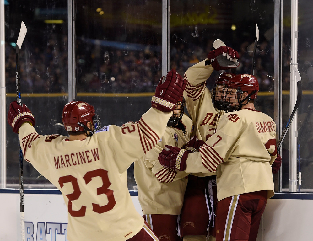 . Denver Pioneers forward Dylan Gambrell (7) celebrates his goal with Denver Pioneers forward Danton Heinen (20) and Denver Pioneers forward Matt Marcinew (23) in the third period against Colorado College Tigers during the Battle On Blake February 20, 2016 at Coors Field. Denver Pioneers defeated Colorado College Tigers 4-1 in front of 35,144 hockey fans.  (Photo By John Leyba/The Denver Post)