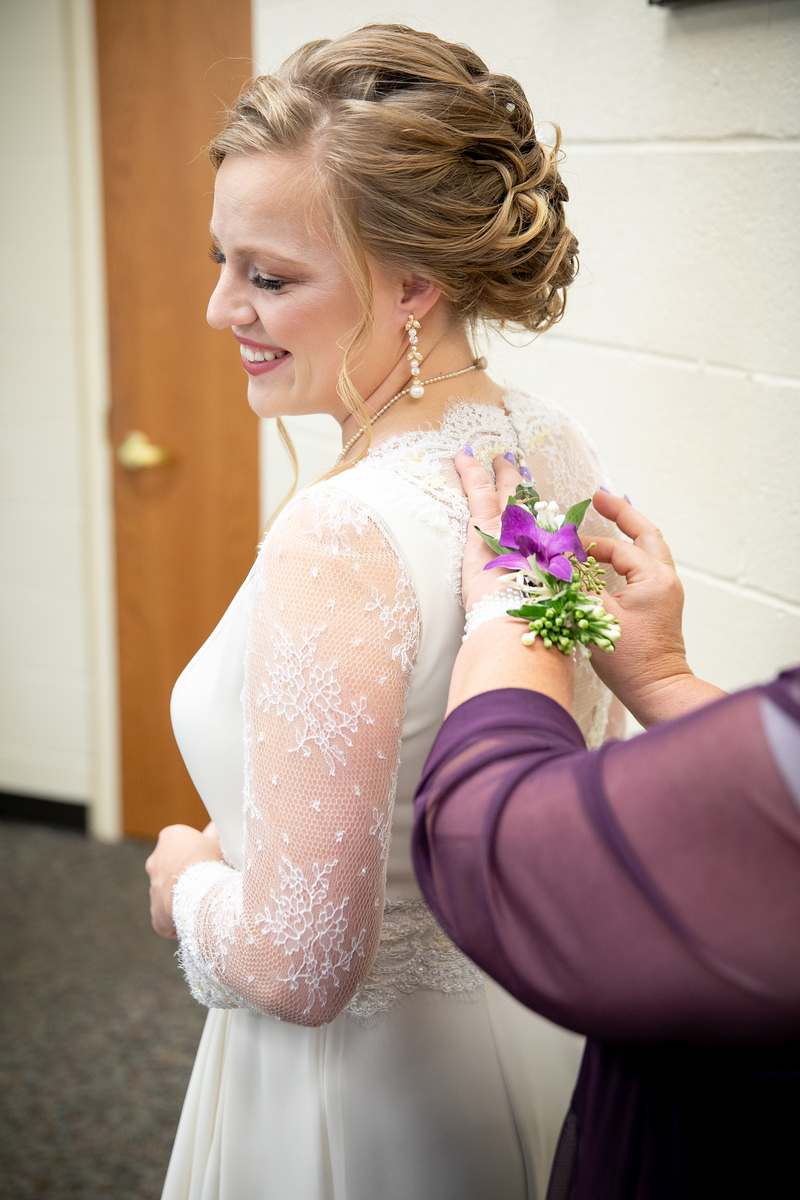 a bride getting her lace wedding dress zipped up by her mother on her wedding day.