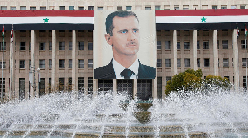 . A picture of Syria\'s President Bashar al-Assad is seen on the central bank building in Damascus, on February 24, 2012. Syria\'s central bank has largely abandoned efforts to support the value of its currency in order to protect its remaining foreign exchange reserves, which have been slashed by the country\'s civil war, bankers and analysts say.  REUTERS/Khaled al-Hariri/Files