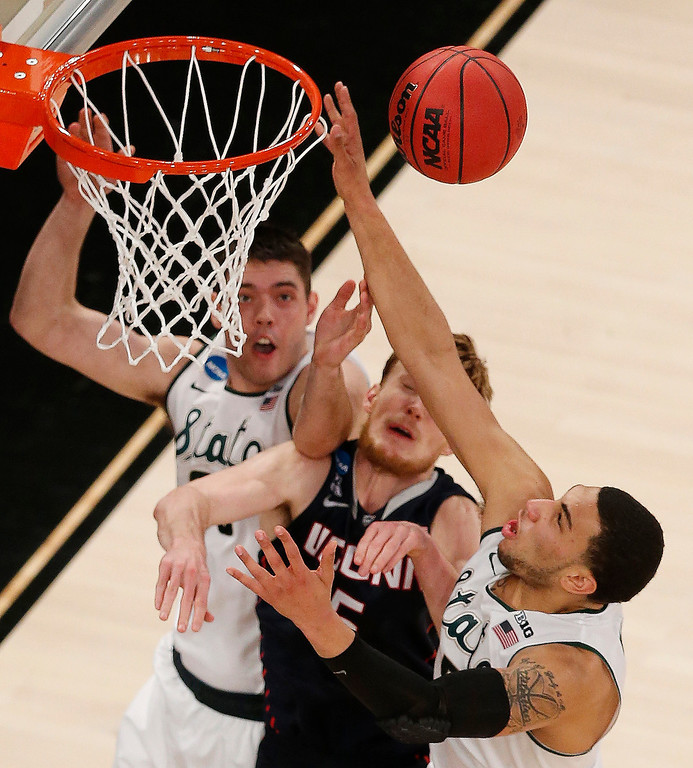 . Connecticut forward Niels Giffey, center, goes up for an offensive rebound against Michigan State forward Kenny Kaminski, left, and guard Denzel Valentine during the second half in a regional semifinal at the NCAA college basketball tournament on Sunday, March 30, 2014, in New York. (AP Photo/Julio Cortez)