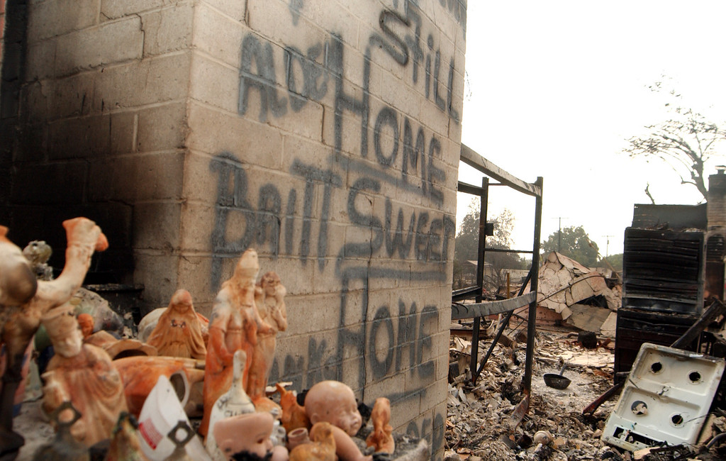 ". Ten years ago this month the arson caused Old Fire, fanned by Santa Ana winds burned thousands of acres, destroyed hundreds of homes and caused six deaths. The fire burned homes in San Bernardino, Highland, Cedar Glen, Crestline, Running Springs and Lake Arrowhead and forced the evacuation of thousand of residents. A sign spray painted on the wall of a San Bernardino home destroyed by fire reads ""Still Home Sweet Home.\"" (Staff file photo/The Sun)"