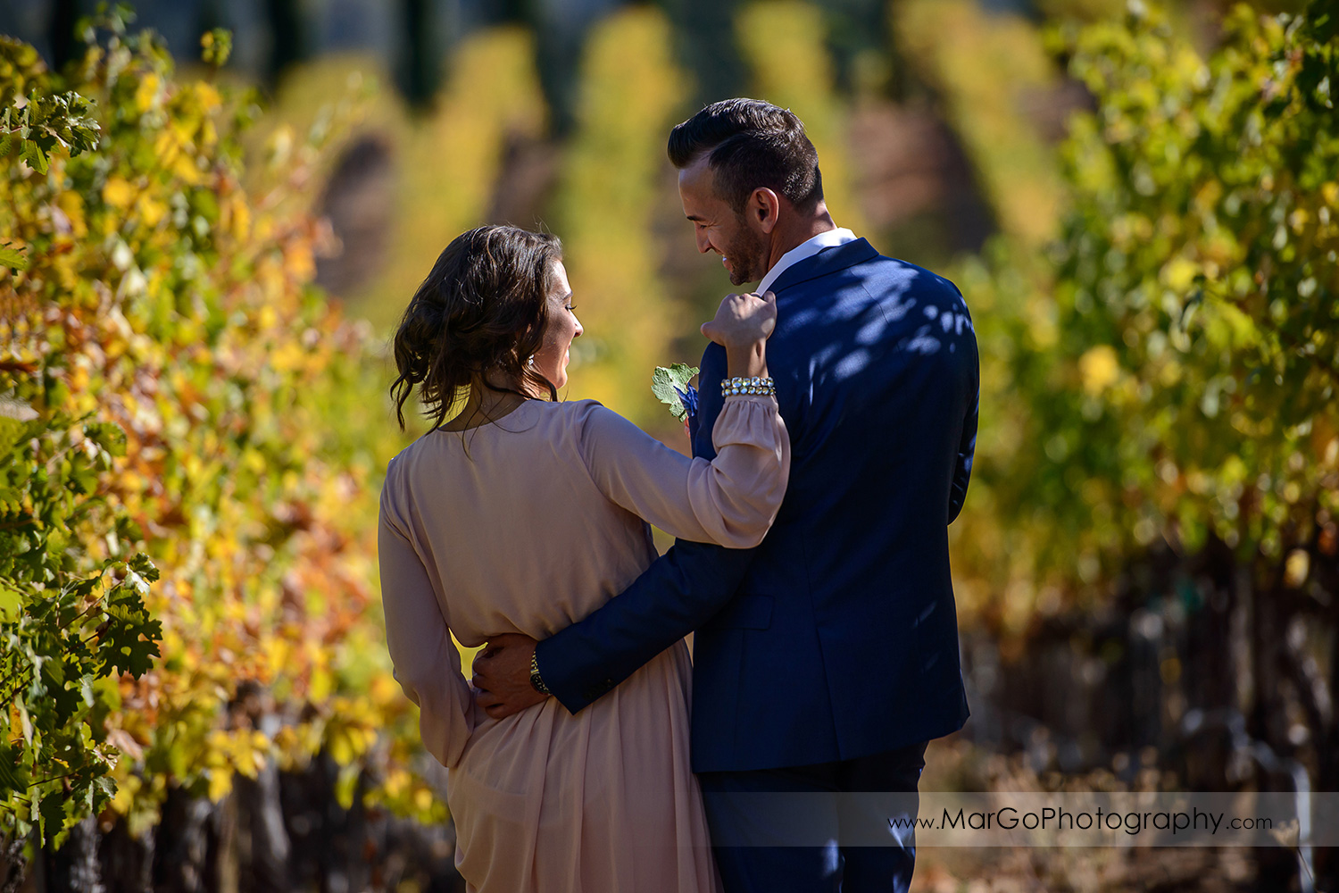 woman in pink dress and man in blue suit holding walking in vineyard during Napa Valley engagement session at Castello di Amorosa in Calistoga
