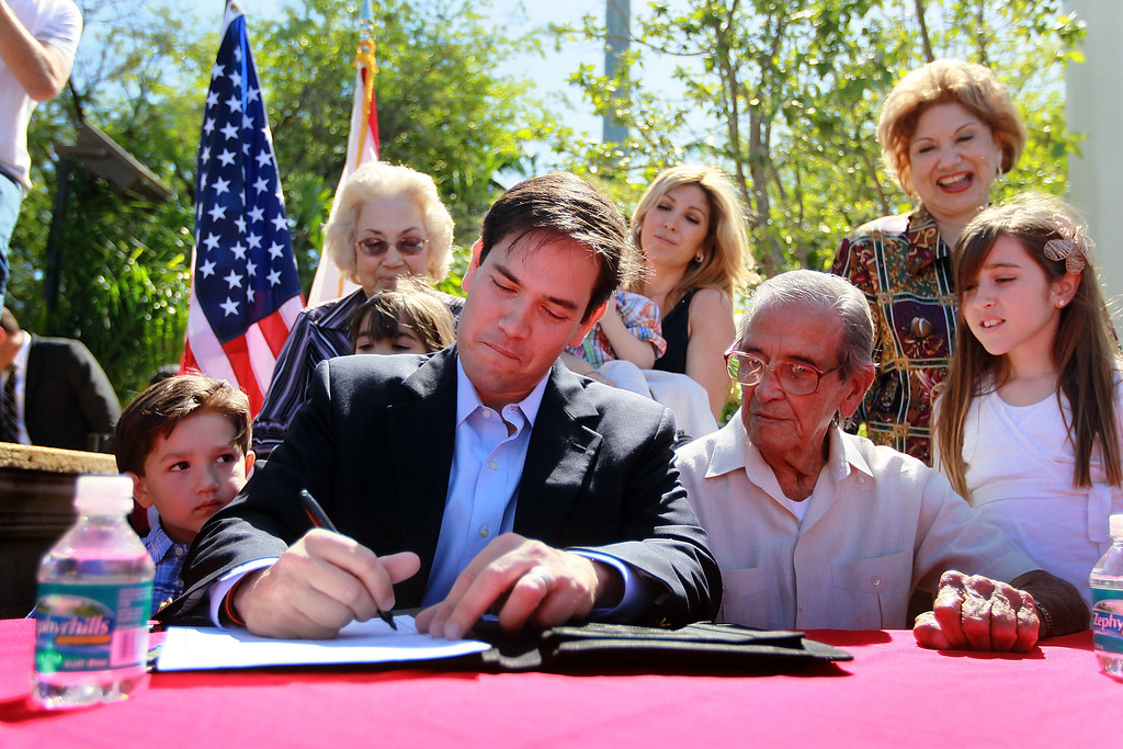 . Marco Rubio (3rd L) puts pen to paper as he sits with his son, Anthony Rubio (L), father Mario Rubio (3rd R) and daughter Amanda Rubio (R) as he signs election documents officially qualifying him as a Republican candidate for the U.S. Senate on April 27, 2010 in Miami, Florida.  (Photo by Joe Raedle/Getty Images)