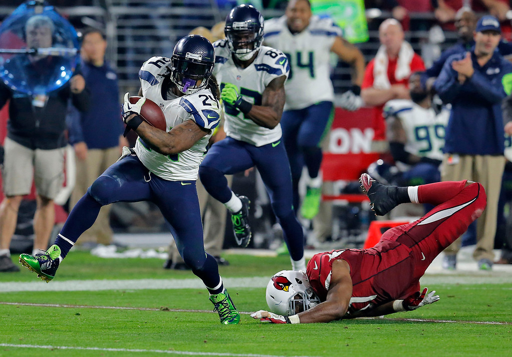 . Seattle Seahawks running back Marshawn Lynch (24) breaks free from Arizona Cardinals outside linebacker Alex Okafor (57) for a touchdown run during the second half of an NFL football game, Sunday, Dec. 21, 2014, in Glendale, Ariz. (AP Photo/Rick Scuteri)