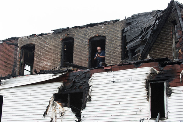 06/25/19 Wesley Bunnell   Staff A fire broke out at a three floor residence at 39 South Whiting St in New Britain on Monday June 24, 2019 at approximately 8pm with firefighters on the scene until approximately 4am Tuesday morning. Fire investigators look out from a third floor rear window which was previously covered as the remnants of the staircase roof hang on the right hand corner of the building.