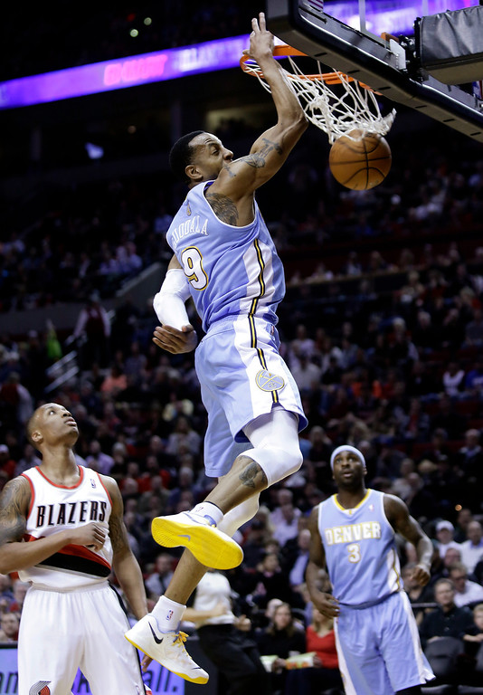 . Denver Nuggets guard Andre Iguodala, center, scores on a fast break as Portland Trail Blazers guard Damian Lillard, left, and Nuggets guard Ty Lawson watch during the first quarter of an NBA basketball game in Portland, Ore., Wednesday, Feb. 27, 2013. (AP Photo/Don Ryan)