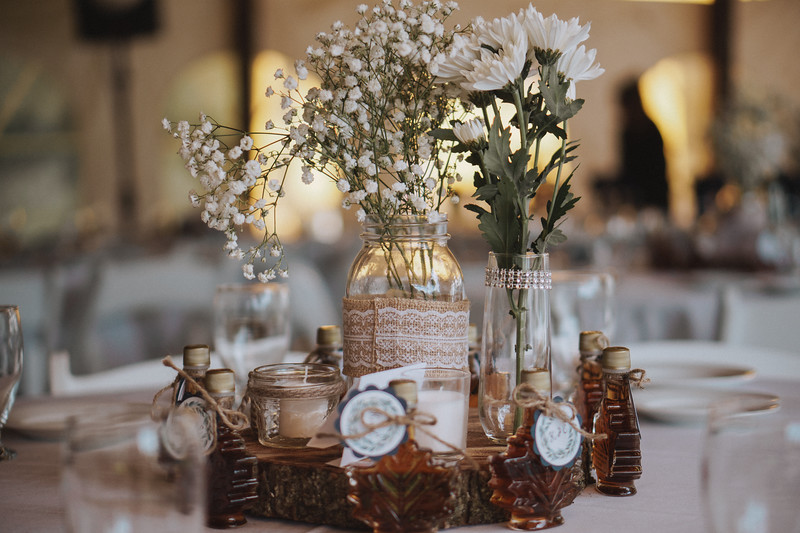 A burlap wrapped mason jar holds flowers as a centerpiece surrounded by candles and maple leaf shaped bottles of syrup.