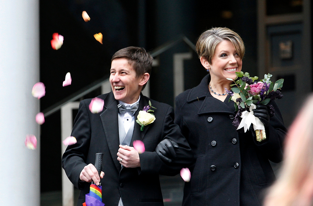 . Newlyweds Heather Laird, left, and Dawn Rains smile as flower petals are tossed their way as they depart Seattle City Hall, Sunday, Dec. 9, 2012, in Seattle. (AP Photo/Elaine Thompson)