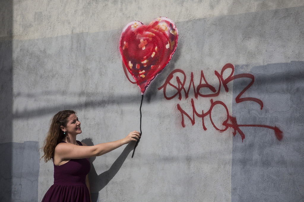 . A woman poses with a piece of street art, which depicts a heart-shaped balloon covered in bandages and was allegedly done by the street artist Banksy, on October 7, 2013 in the Red Hook neighborhood of the Brooklyn borough of  New York City. The piece was defaced with red spray paint shortly after being completed.  (Photo by Andrew Burton/Getty Images)