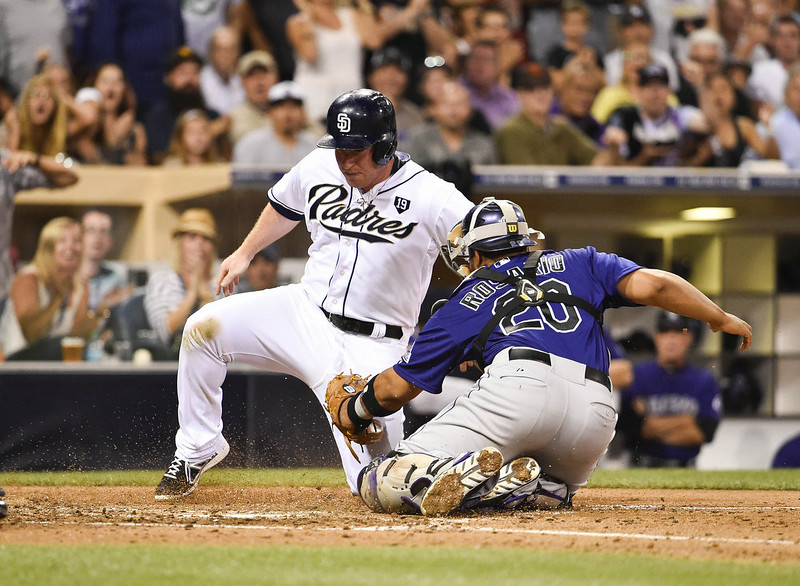 . Jedd Gyorko #9 of the San Diego Padres is tagged out at the plate by Wilin Rosario #20 of the Colorado Rockies during the fourth inning of a baseball game at Petco Park August, 11, 2014 in San Diego, California.  (Photo by Denis Poroy/Getty Images)