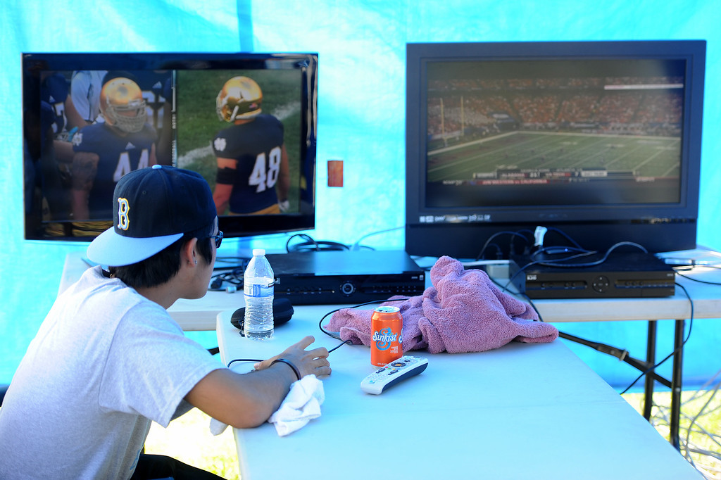 . Ryan Harada watches a couple TVs before the UCLA-Nevada game at the Rose Bowl, Saturday, August 31, 2013. (Michael Owen Baker/L.A. Daily News)