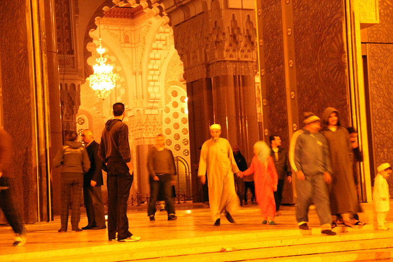 nighttime outside hassan II mosque, worshippers coming out. casablanca