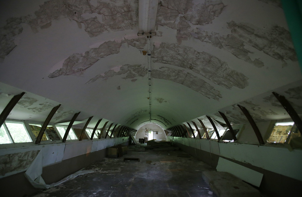 """. In this Oct. 18, 2014 photo, the interior of concrete structures called \""""Quonset huts\"""" crumbles inside the Subic Bay Freeport Zone, Zambales province, northern Philippines. Naval Station Subic Bay used to be one of the largest U.S. military base outside the American mainland. It was partly damaged during the eruption of Mount Pinatubo forcing American troops from the more severely damaged Clark Air Base to relocate at Subic. It was closed in 1992 after the Philippine Senate voted not to extend the lease on the facility. (AP Photo/Aaron Favila)"""