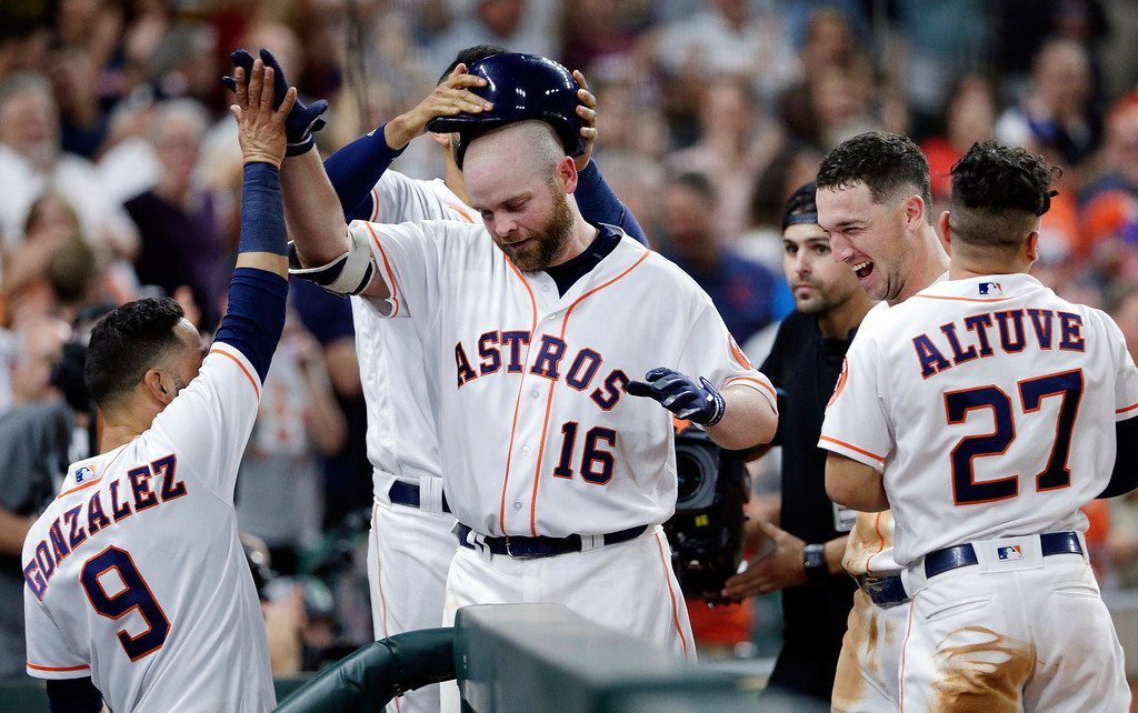 . Houston Astros\' Brian McCann (16) is congratulated as he enters the dugout by, from left, Marwin Gonzalez (9), Carlos Correa, removing helmet, Alex Bregman and Jose Altuve (27) after McCann\'s two-run home run during the seventh inning of a baseball game against the Cleveland Indians, Sunday, May 20, 2018, in Houston. (AP Photo/Michael Wyke)