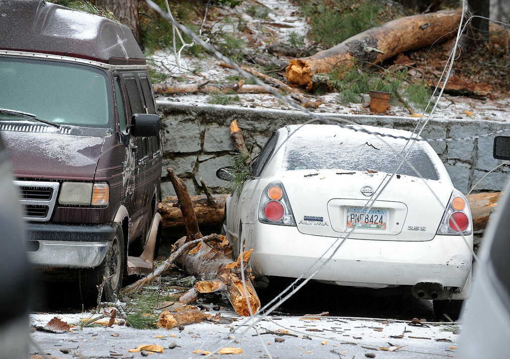 . A downed power line damages several vehicles and disrupted electricity for 200 residents at the Marquis at Lenox apartments during a winter storm on Wednesday, Feb. 12, 2014, in Atlanta. Georgia utility companies say more than 177,000 customers were without power as ice coated trees and brought branches and power lines down on Wednesday. (AP Photo/David Tulis)
