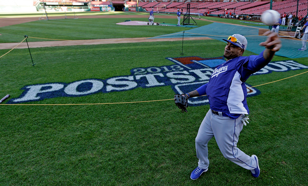 . Los Angeles Dodgers outfielder Carl Crawford  throws before Game 1 of the National League baseball championship series against the St. Louis Cardinals Friday, Oct. 11, 2013, in St. Louis. (AP Photo/Charlie Neibergall)