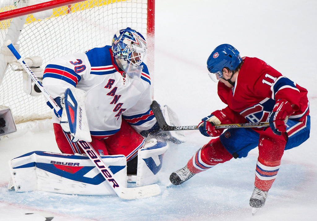 . Montreal Canadiens\' Brendan Gallagher slides in on New York Rangers\' goaltender Henrik Lundqvist, left, during the second period in Game 2 of the NHL hockey Eastern Conference final Stanley Cup playoff action in Montreal, Monday, May 19, 2014. (AP Photo/The Canadian Press, Graham Hughes)