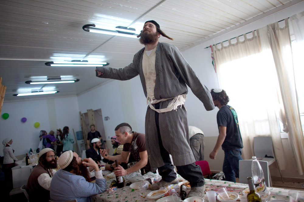 . A Jewish settler wears a costume and dances on a table as they celebrate the Jewish festival of Purim February 24, 2013 at the settlement outpost of Havat Gilad, West Bank. The carnival-like Purim holiday is celebrated with parades and costume parties to commemorate the deliverance of the Jewish people from a plot to exterminate them in the ancient Persian empire 2,500 years ago, as described in the Book of Esther. (Photo by Uriel Sinai/Getty Images)