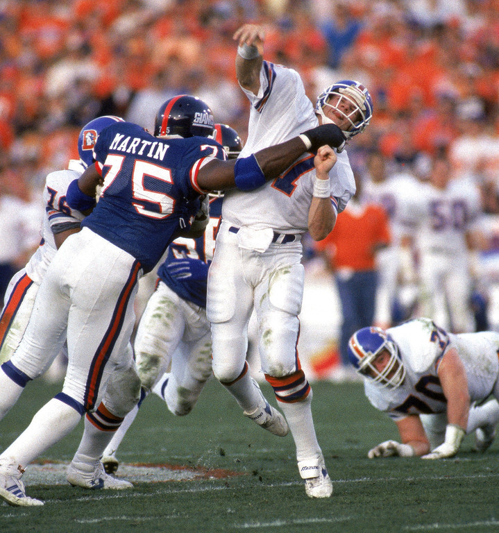 . Quarterback John Elway #7 of the Denver Broncos gets rid of the ball just before getting hit by defensive end George Martin #75 of the New York Giants during Super Bowl XXI at the Rose Bowl on January 25, 1987 in Pasadena, California.  The Giants won 39-20.  (Photo by George Rose/Getty Images)