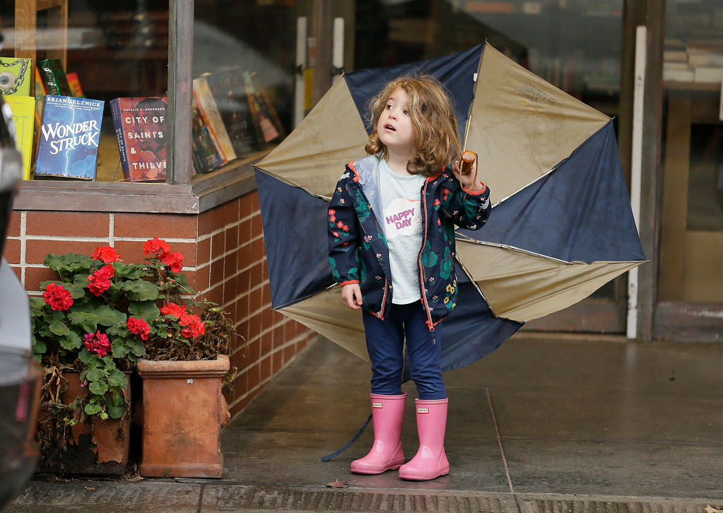 . Three-year-old Emerson Cassidy takes cover from the rain in a storefront entryway Monday, Feb. 20, 2017, in San Anselmo, Calif. Heavy downpours are swelling creeks and rivers and bringing threats of flooding in California\'s already soggy northern and central regions. The National Weather Service map shows floods, snow and wind advisories for the northern part of the state. (AP Photo/Eric Risberg)