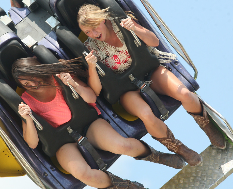 . Kelsey Varano, 14, and Sarah Bordiuk , 14 both of Oriskany hold on as they ride the Twin Flip on the midway at the Boonville Oneida County Fair on Tuesday, July 22, 2014 in Boonville. the fair runs through Sunday, July 27, 2014.  JOHN HAEGER-ONEIDA DAILY DISPATCH @ONEIDAPHOTO ON TWITTER