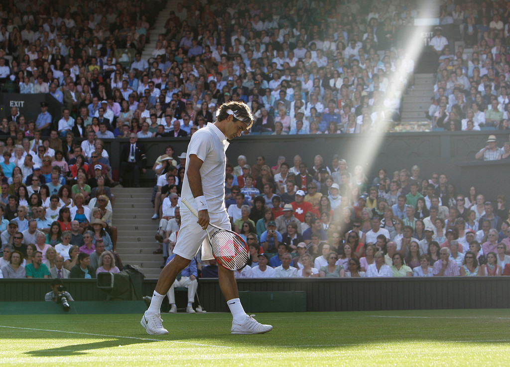 . In this Wednesday, June 25, 2008 file photo made by Associated Press photographer Anja Niedringhaus, Switzerland\'s Roger Federer walks across the court as a shaft of late afternoon light illuminates the Centre Court during his second round match against Sweden\'s Robin Soderling at Wimbledon, England.  (AP Photo/Anja Niedringhaus, File)
