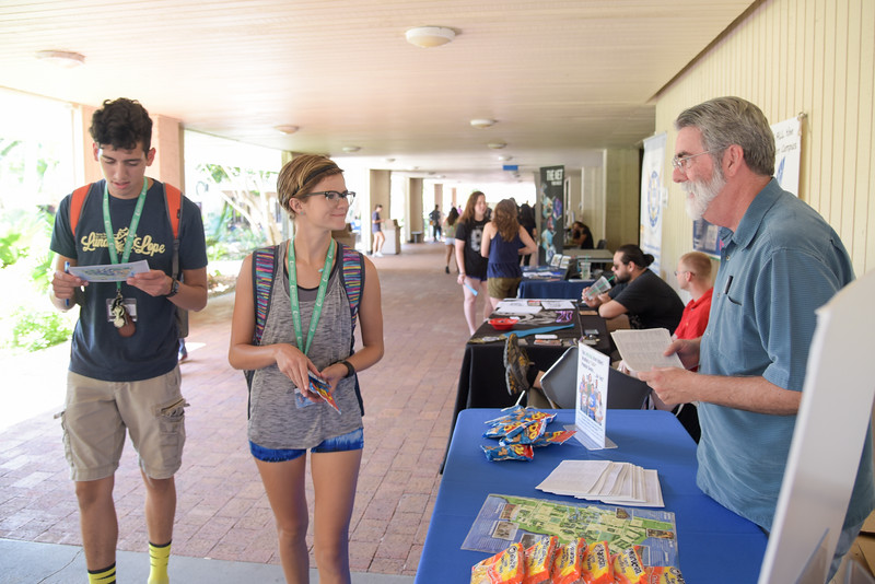 Josh Salazar (left), Morgan McCutchen are greeted by Jeffrey Janko during the Waves of Welcom event in the breezeway.