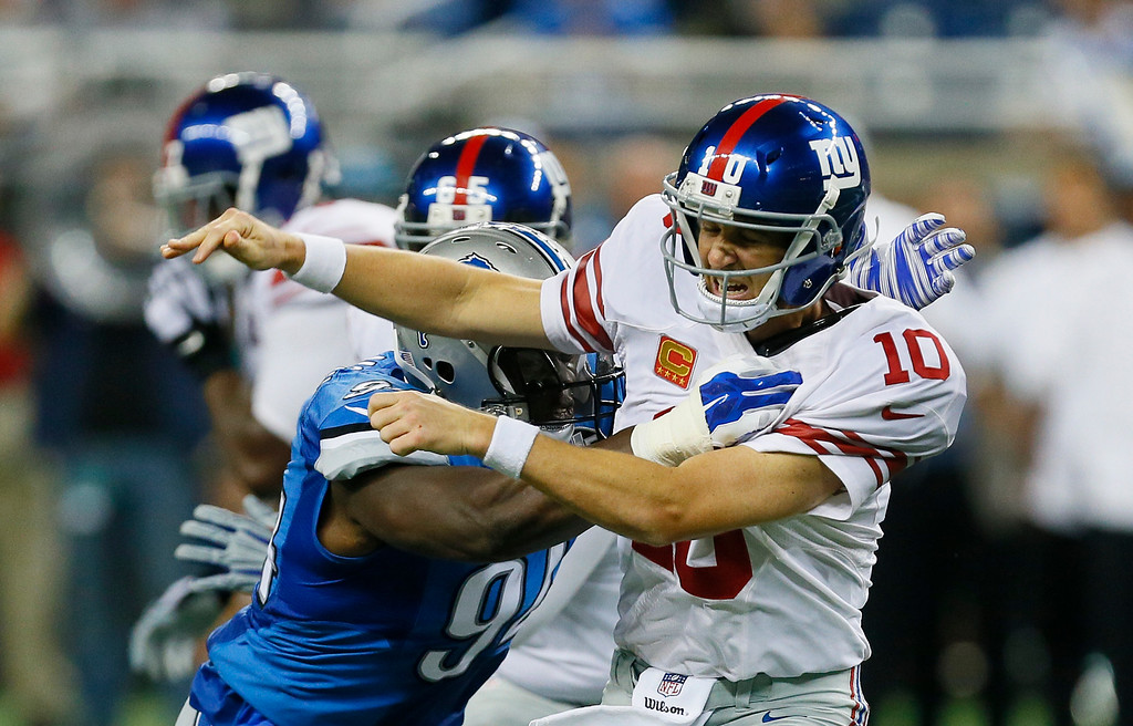 . New York Giants quarterback Eli Manning (10) is knocked down by Detroit Lions defensive end Ezekiel Ansah (94) during the second quarter of an NFL football game in Detroit, Monday, Sept. 8, 2014. (AP Photo/Paul Sancya)