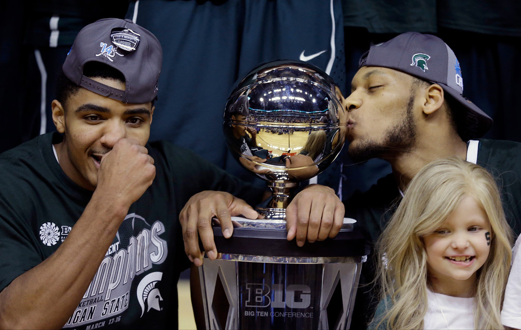 ". FILE - In this March 16, 2014 file photo, Michigan State\'s Gary Harris, left, poses with the championship trophy as Adreian Payne kisses it after they  defeated Michigan 69-55 in an NCAA college basketball game in the championship of the Big Ten Conference tournament in Indianapolis. Lacey Holsworth, who is battling cancer,  smiles at right foreground. The father of  8-year-old Lacey Holsworth, who befriended Michigan State basketball star Adreian Payne says his daughter has died. Matt Holsworth says Lacey Holsworth died at their St. Johns, Mich., home late Tuesday, April 8, 2014, ""with her mommy and daddy holding her in their arms.\""(AP Photo/Michael Conroy)"