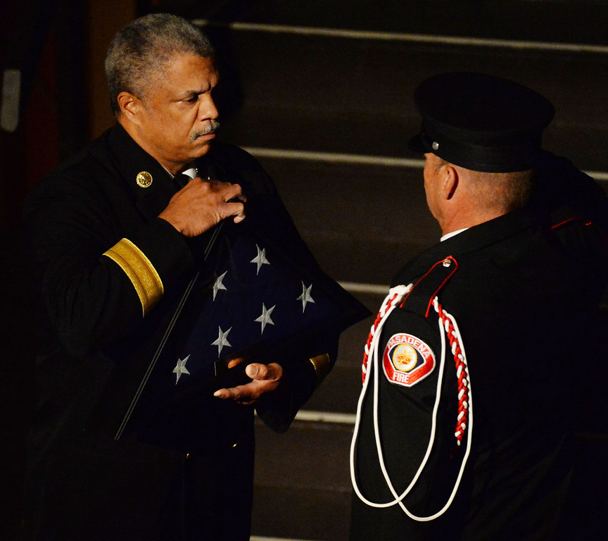 . Pasadena Fire Chief, Calvin E. Wells, left, prepares to present the flag to the Tennant family during a celebration of life service for former Pasadena Fire dept. Capt. and California State fire marshall, John Tennant at the Pasadena Civic Auditorium in Pasadena, Calif., on Wednesday, Feb. 5, 2014. (Keith Birmingham Pasadena Star-News)