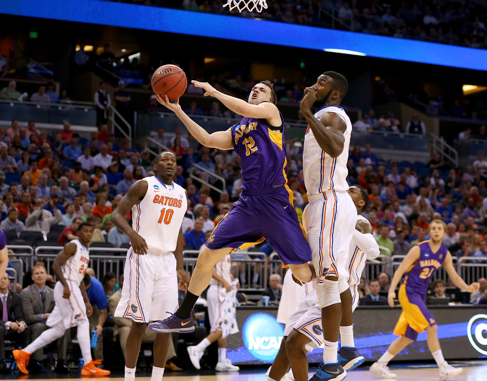 . ORLANDO, FL - MARCH 20:  Peter Hooley #12 of the Albany Great Danes goes up for a shot against Patric Young #4 of the Florida Gators in the first half during the second round of the 2014 NCAA Men\'s Basketball Tournament at Amway Center on March 20, 2014 in Orlando, Florida.  (Photo by Mike Ehrmann/Getty Images)