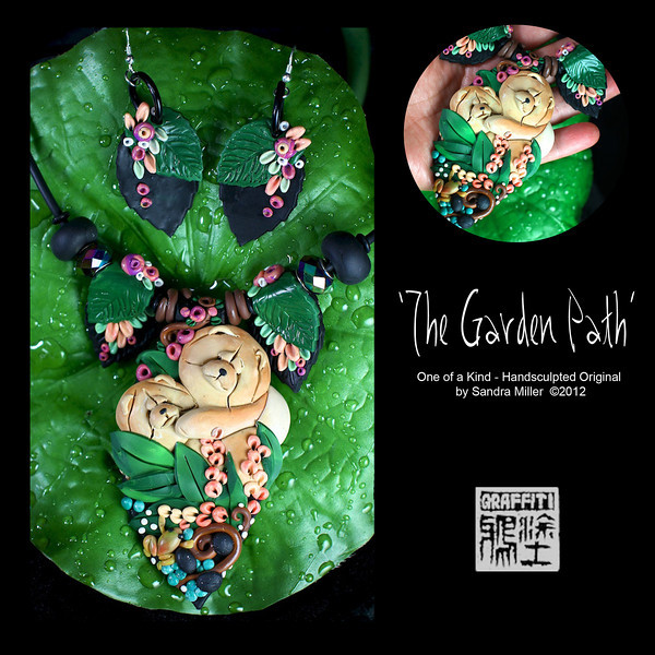 """THE GARDEN PATH- CLICK HERE TO VIEW VIDEO DESCRIPTION IN A NEW WINDOW      This signature necklace and earrings set is one of my favorite sets EVER!     There is literally a garden party going on here with the chows being the life of the party.      The necklace was created in five distinct pieces, when strunk on the neoprene cord, adjust to fit the neckline like you were born wearing it!. The central long pendant features the two  romping Chows I named """"Zoie and Zeus"""", and the little froggy's name is """"Glurp"""" .  All  of the garden  elements have been sculpted by hand on the end of a knitting needle and with a sewing needle      I used my 3-D watercolor technique to blush color into the chow's shaded red coats, as well as some of the flowers.  The leaves with clusters of flowers to the left and right of the centerpiece are also hand sculpted and created as beads with a channel running through the center      Then to make a nice separation between the centerpiece and the leaves I sculpted little vine beads to entwine the cord      Two large aurora borealis crystals were added to the beadwork as well as the hand sculpted black beads to finish off the ends      The earrings are large but practically weightless as is the necklace..... you hardly know you're wearing either one of them.      This is my most elaborate piece of the 2012 Trunk Show.   It is truly a statement,  it is one-of-a-kind, and comes in its own special  presentation case to use for traveling to the National Specialty or wherever you plan to bring Zoie,Zeus and Glurp on a roadtrip!!     PENDANT MEASURES   4 x 2 1/2"""" Neoprene cord is finished at the back with chain and adjusts from 16-20"""" long.  EARRINGS MEASURE 1 1/2"""""""
