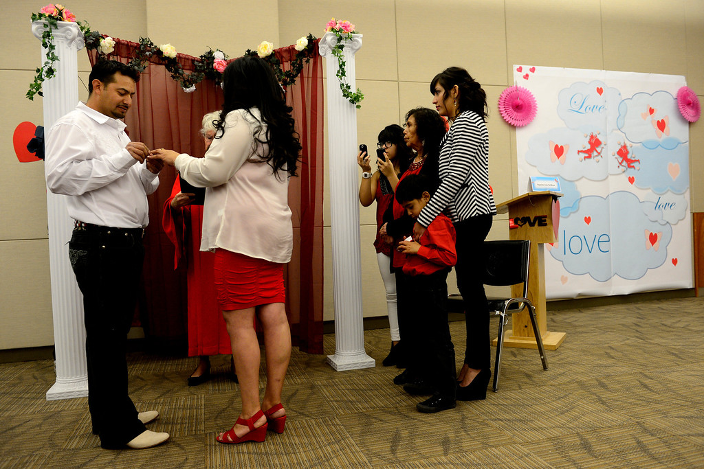. DENVER, CO - FEBRUARY 14: Joel Herrera places a ring on the finger of Sylvenvestra Rodriguez during a Valentine\'s Day marriage celebration at the Denver Clerk and Recorder\'s office. Couples applying for marriage licenses received gift bags containing gift certificates to local restaurants among other treats to celebrate their union. (Photo By AAron Ontiveroz/The Denver Post)