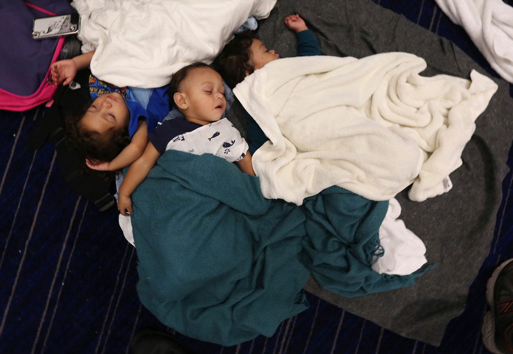 . Robert Salgado, center, sleep with relatives Jesse Alexander Leija, right, and Leliana Salgado on the floor at the George R. Brown Convention Center that has been set up as a shelter for evacuees escaping the floodwaters from Tropical Storm Harvey in Houston, Texas, Tuesday, Aug. 29, 2017. (AP Photo/LM Otero)