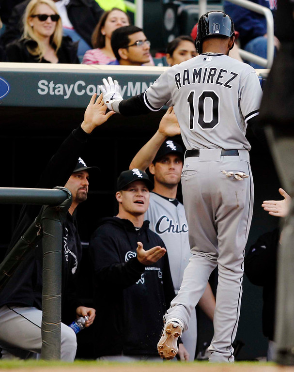 . Chicago White Sox\'s Alexei Ramirez (10) is congratulated by teammates after scoring on Dayan Viciedo\'s sacrifice fly against Minnesota Twins starting pitcher Pedro Hernandez during the first inning of a baseball game, Monday, May 13, 2013, in Minneapolis. (AP Photo/Genevieve Ross)
