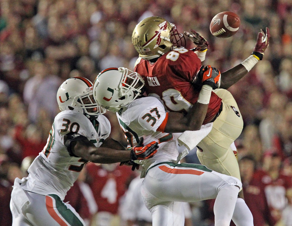 . Miami\'s Ladarius Gunter defends against Florida State\'s Christian Green, who cannot hold on to the ball on an incomplete pass in the first quarter of an NCAA college football game Saturday, Nov. 2, 2013, in Tallahassee, Fla. (AP Photo/Miami Herald, Al Diaz)