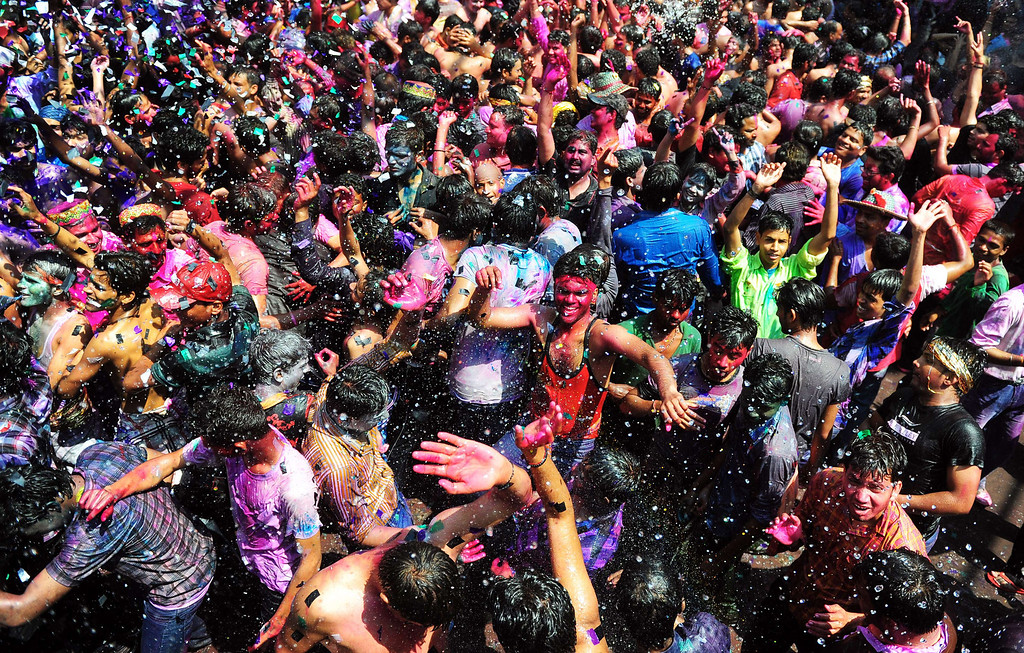 . Indian revelers covered in colored powder dance during Holi festival celebrations in Allahabad on March 17, 2014. Holi, the popular Hindu spring festival of colors is observed in India at the end of the winter season on the last full moon of the lunar month. AFP PHOTO/SANJAY  Kanojia/AFP/Getty Images