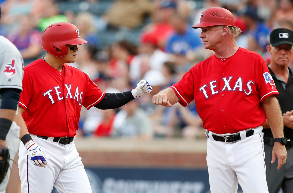 . Texas Rangers\' Shin-Soo Choo, left, celebrates his single with first base coach Steve Buechele, right, during the first inning of a baseball game against the Cleveland Indians, Friday, July 20, 2018, in Arlington, Texas. (AP Photo/Jim Cowsert)