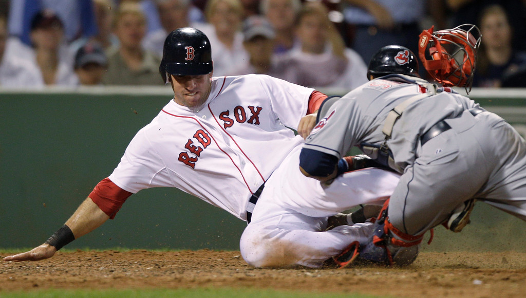 . Boston Red Sox\'s Ryan Kalish collides with Cleveland Indians catcher Carlos Santana, who blocked the plate and tagged out Kalish who was trying to score on a single by Daniel Nava in the seventh inning of a baseball game in Boston, Monday, Aug. 2, 2010. Santana was carted off the field with his left leg in an air cast. (AP Photo/Charles Krupa)
