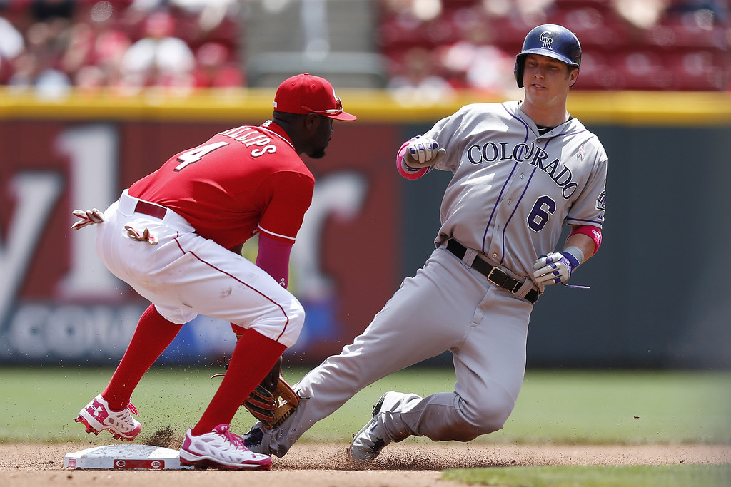 . Corey Dickerson #6 of the Colorado Rockies gets tagged out trying to steal second base by Brandon Phillips #4 of the Cincinnati Reds in the fourth inning of the game at Great American Ball Park on May 11, 2014 in Cincinnati, Ohio. (Photo by Joe Robbins/Getty Images)