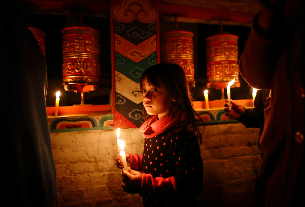 Description of . A Tibetan girl holding a lit candle walks around the Tibetan monastery during a candlelight vigil to show solidarity to Tibetans who have self-immolated, and to mark the 100th anniversary of the 1913 Tibetan Proclamation of Independence, at the Tibetan Refugee Camp in Lalitpur February 13, 2013. A Tibetan monk self-immolated on Wednesday at the premises of the Boudhanath Stupa in Kathmandu. REUTERS/Navesh Chitrakar