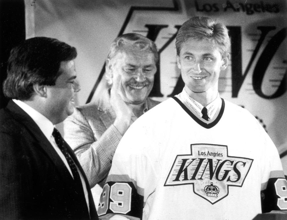 . Kings owner Bruce McNall stands with newest acquisition Wayne Gretzky as Jerry Buss applauds on August 9, 1988.  L.A. Daily News file photo