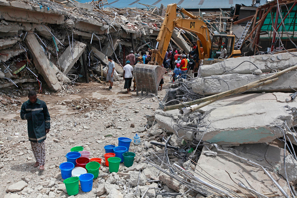 . In this file photo taken on Saturday, Sept. 13, 2014, A rescue worker, left,  walks past buckets of water as the search for survivors continues in the rubble of a collapsed building belonging to the Synagogue Church of All Nations in Lagos, Nigeria. Rescue workers have recovered 46 bodies and rescued 130 survivors from a collapsed shopping mall and guesthouse at the campus of renowned Nigerian preacher T.B. Joshua\'s Synagogue Church of All Nations, the West African nation\'s emergency agency said Monday, Sept. 15, 2014. (AP Photo/Sunday Alamba, File)