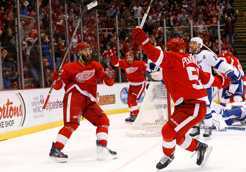. Detroit Red Wings center Joakim Andersson, center rear, celebrates his goal against the Tampa Bay Lightning with teammates Kyle Quincey, left, and  Teemu Pulkkinen, right,  in the second period of an NHL hockey game in Detroit Saturday, March 28, 2015. (AP Photo/Paul Sancya)