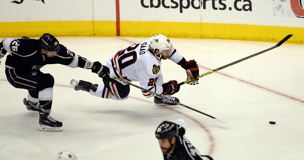 . The Blackhawks� Brandon Saad #20 looses his feet as the Kings� Slava Voynov #26 moves in during Game 6 of the Western Conference finals at the Staples Center on Friday, May 30, 2014. The Blackhawks beat the Kings 4-3. (Photo by Hans Gutknecht/Los Angeles Daily News)